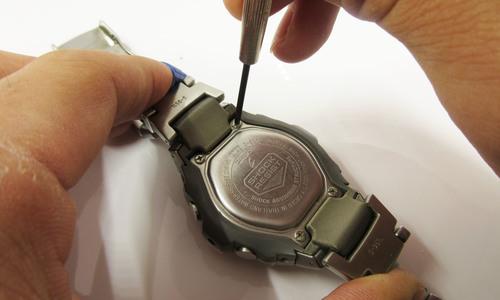 デジタル時計の裏ぶたを閉めている