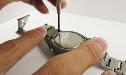 デジタル時計の裏ブタネジを回している写真