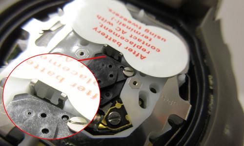 電池のカバーの隙間にピンセットを差し込んだ写真