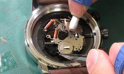 引っかけタイプの時計に新しい電池を入れている
